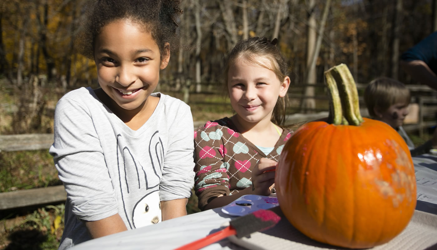 two girls painting a pumpkin