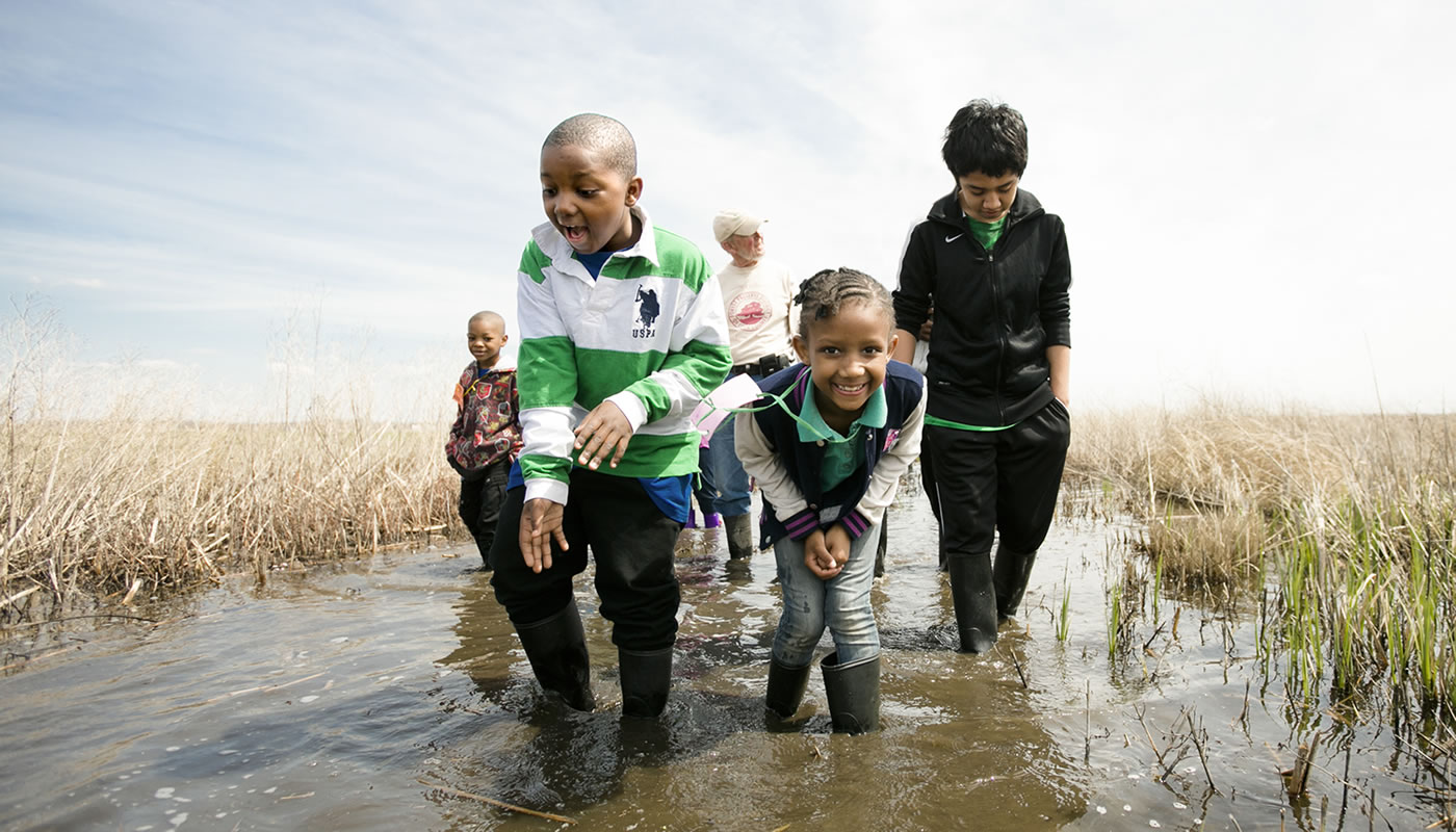 children exploring a wetland at Bartel Grassland