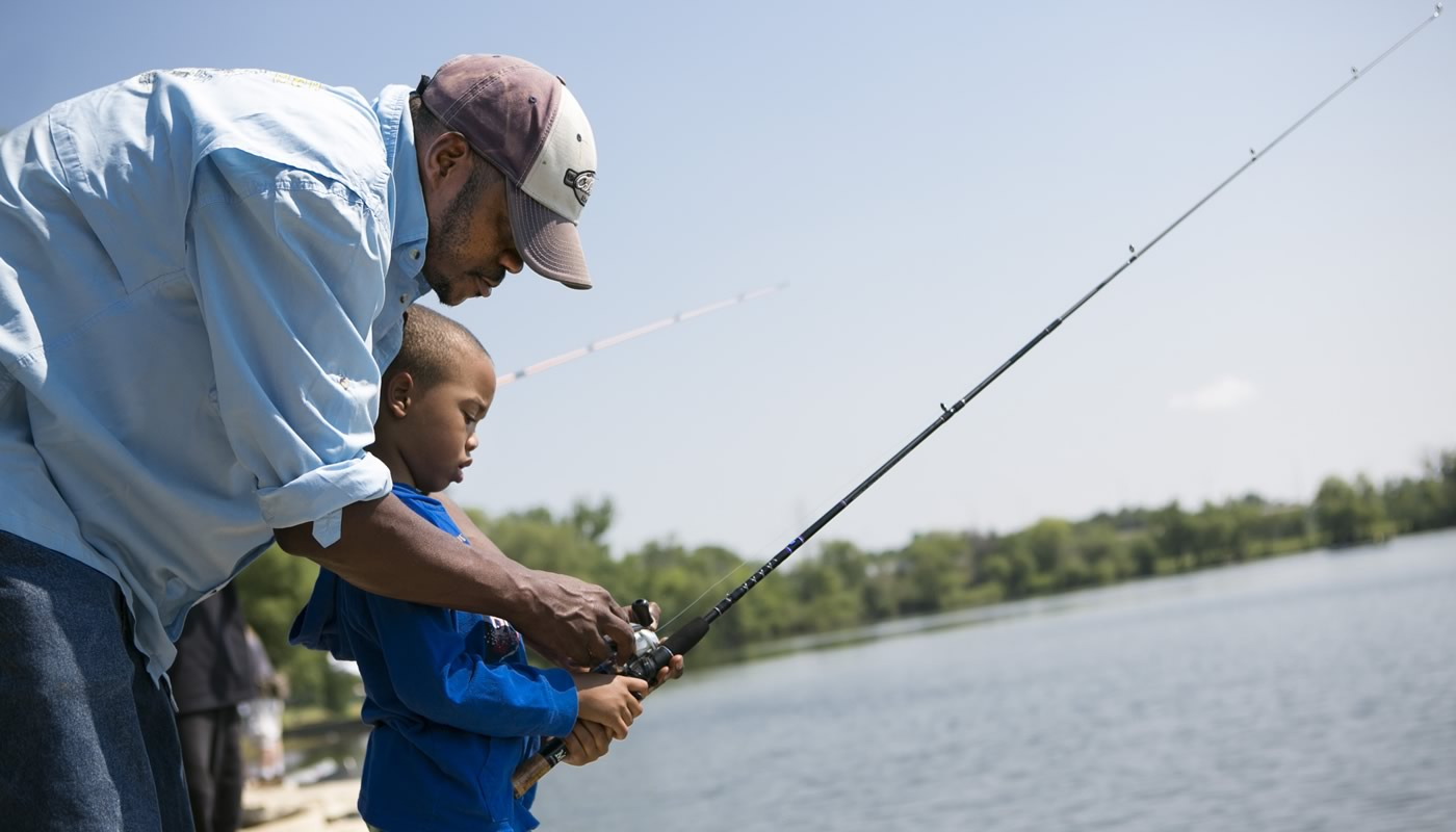 an adult and child fishing at Wampum Lake during Kids Fest event