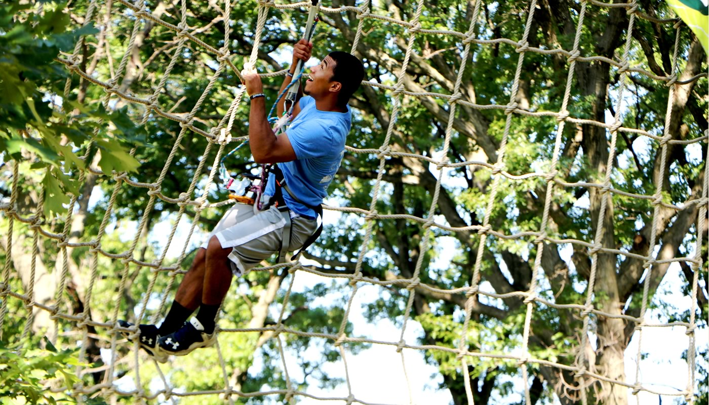 a person climbing a net on the Go Ape Tree Top Adventure Course in Bemis Woods