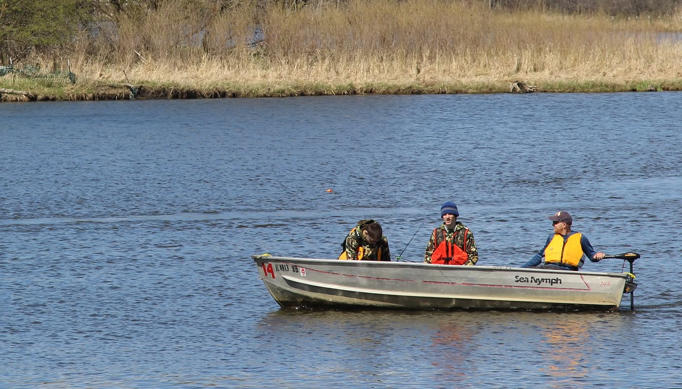 Three people fishing from a row boat with an electric trolling motor at Busse Reservoir