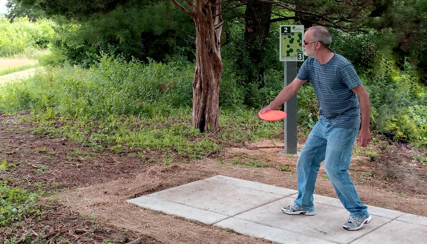 a person playing disc golf at Rolling Knolls