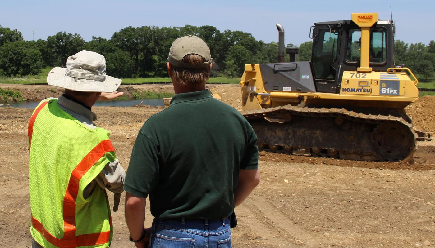 two people talking near a bulldozer