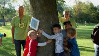 General Superintendent Arnold Randall, President Toni Preckwinkle and children hugging a tree during an event.