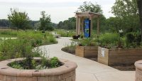 a garden with accessible raised beds, paved trail and interpretive signs