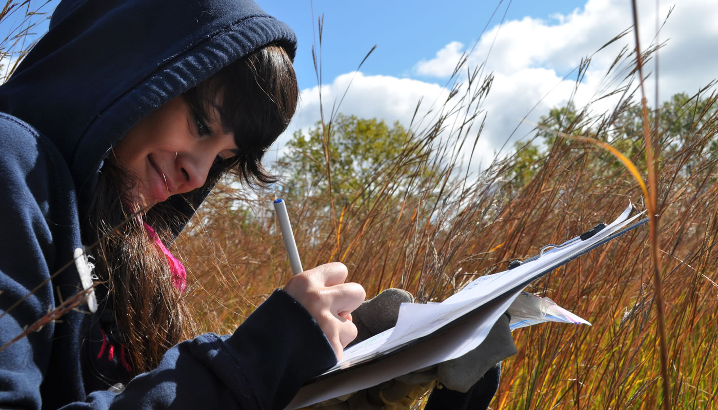 a person writing ecological monitoring observations on a clipboard outside at Beaubien Woods as part of the Calumet Is My Back Yard Program.