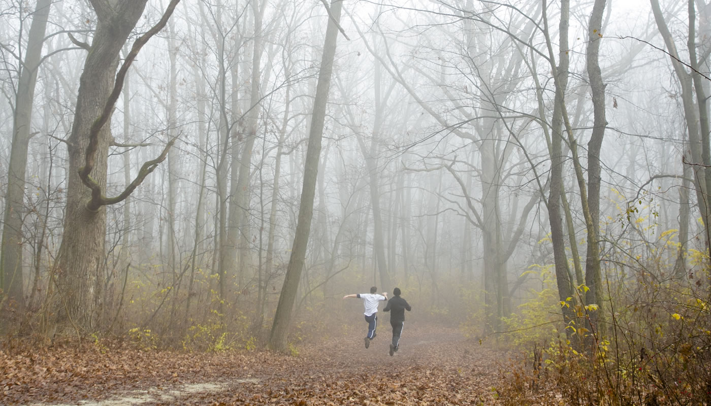 two people running on a foggy day at Cap Sauers Holding Nature Preserve