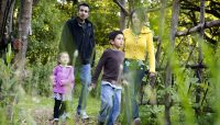 a family exploring the trails at Crabtree Nature Center