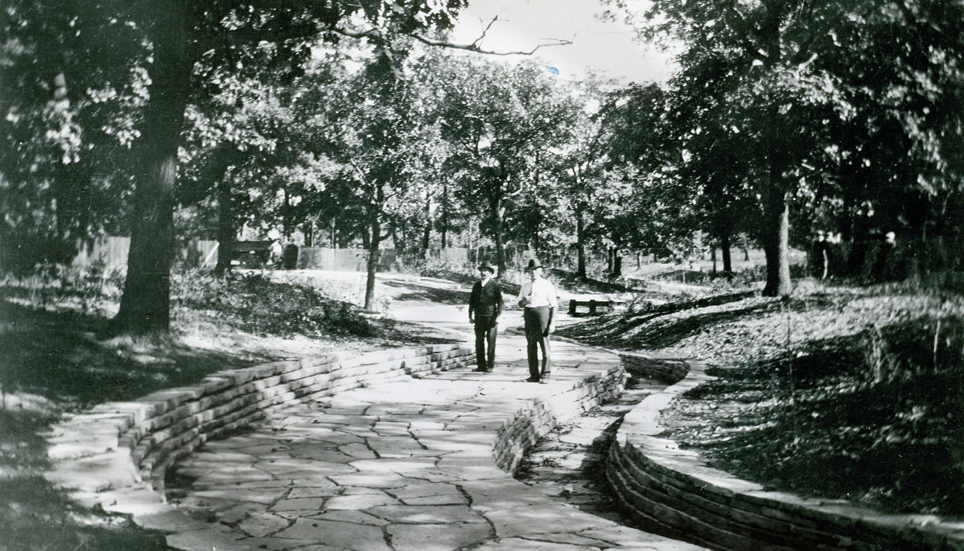 historic photo of two people posing with the Civilian Conservation Corps built limestone aqueducts at Dan Ryan Woods