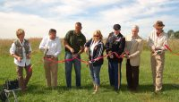 Ribbon cutting at Orland Grassland - Left to right: Pat Hayes (Orland Grassland Volunteers), Gerald Adelmann (Openlands), Arnold Randall (FPCC), Forest Preserves Commissioner Elizabeth Gorman, Col. Christopher Drew (Army Corps), Mayor Dan McLaughlin (Village of Orland Park), Stephen Packard (founding director of Audubon Chicago Region)