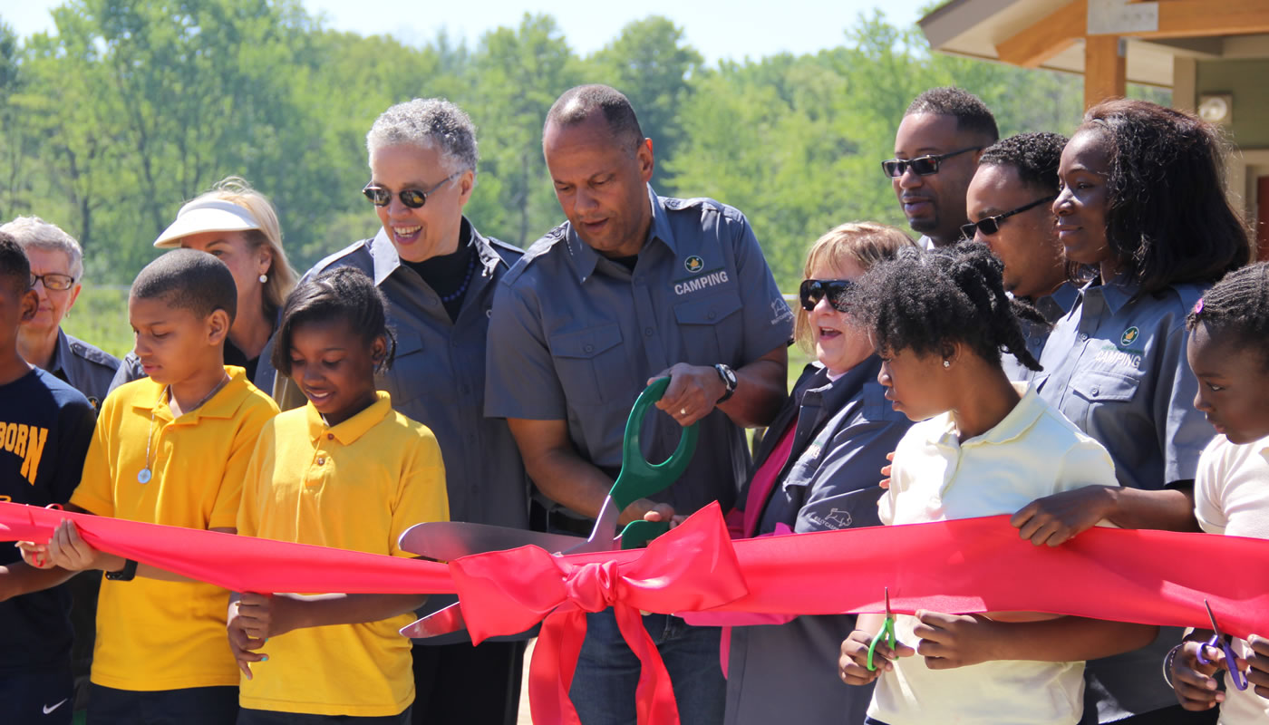 People cutting a ribbon at the opening of Camp Shabbona Woods.