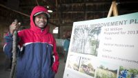 a person poses next to a poster with details of the Forest Preserves Camping Master Plan