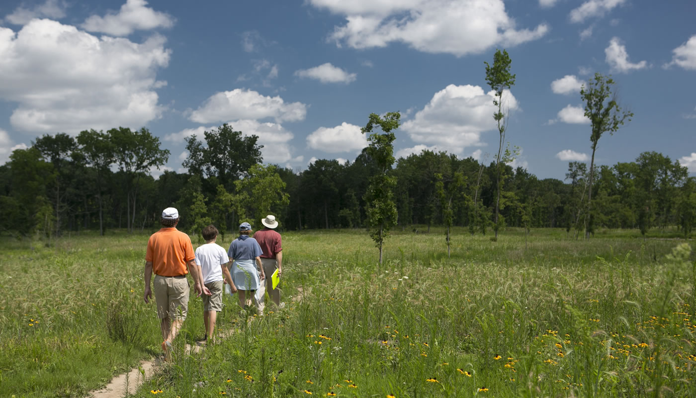 Four people walking along a primitive trail at Deer Grove-East