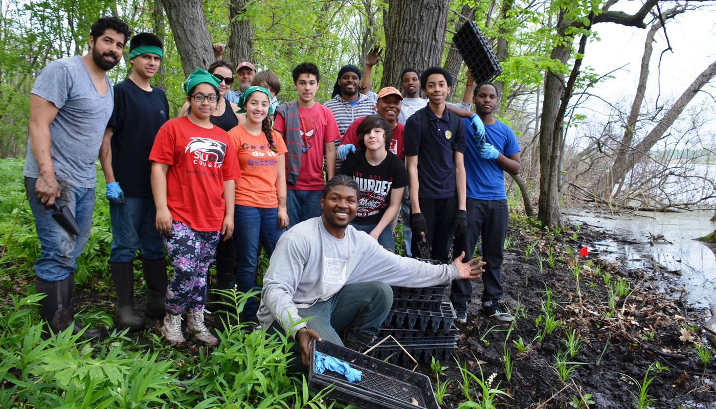 a group of volunteers posing near wetland plants they just finished planting