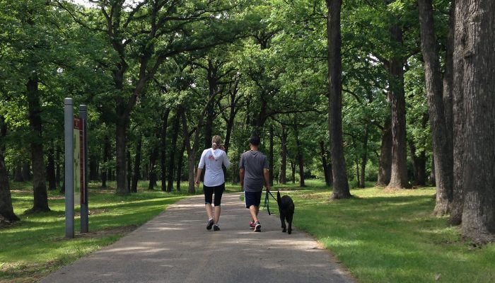 two people walking a dog on the Tinley Creek Trail at Yankee Woods