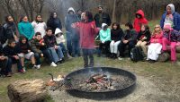 A Forest Preserves staff member showing how to light a fire in front of a group at a Camping 101 event.