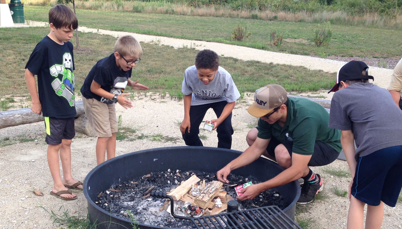 A Forest Preserves staff member showing how to light a fire in front of a small group at a Camping 101 event.