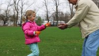 a young girl picks up trash in a picnic grove and hands it to her grandfather