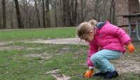 a young girl picks up trash in a picnic grove