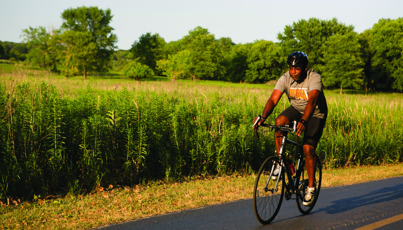 a person riding a bike on the paved trail at Busse Woods