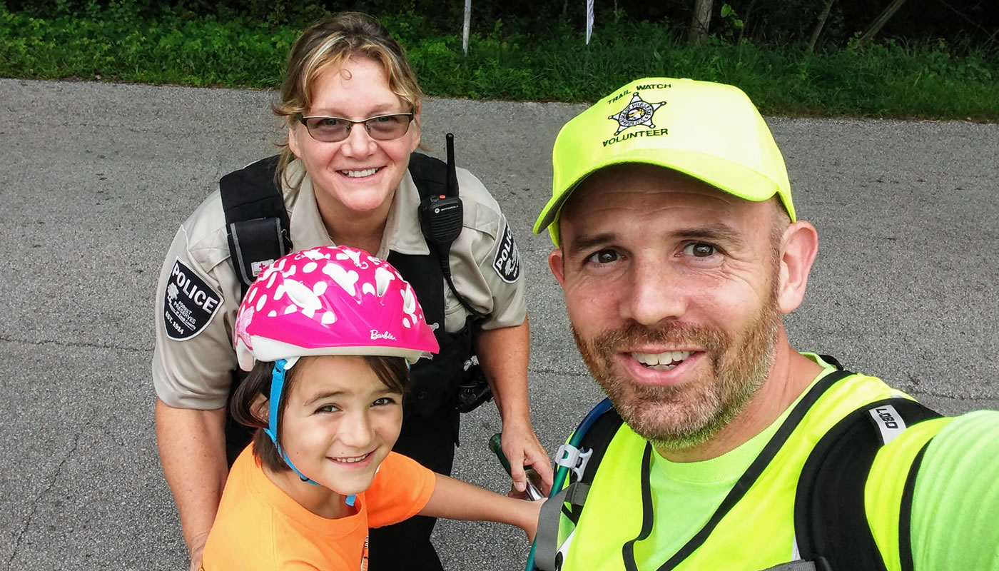 a trail watch volunteer, Forest Preserves Police Officer and child pose for a photo