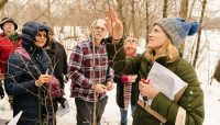 people around a tree in winter, learning how to identify it. Photo by Dan Kasberger.