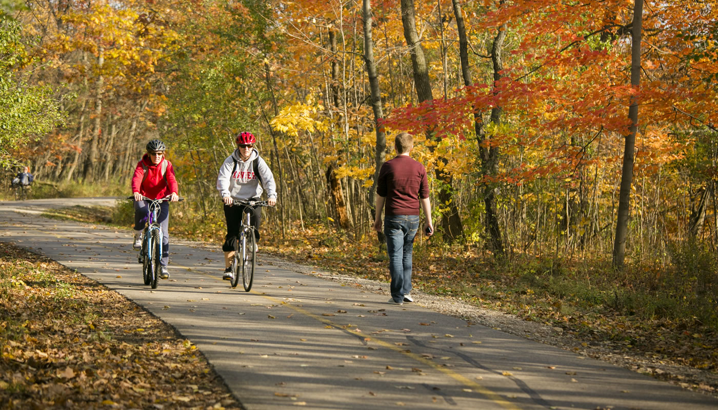 bike riders and a walker on the North Branch Trail at Caldwell Woods.