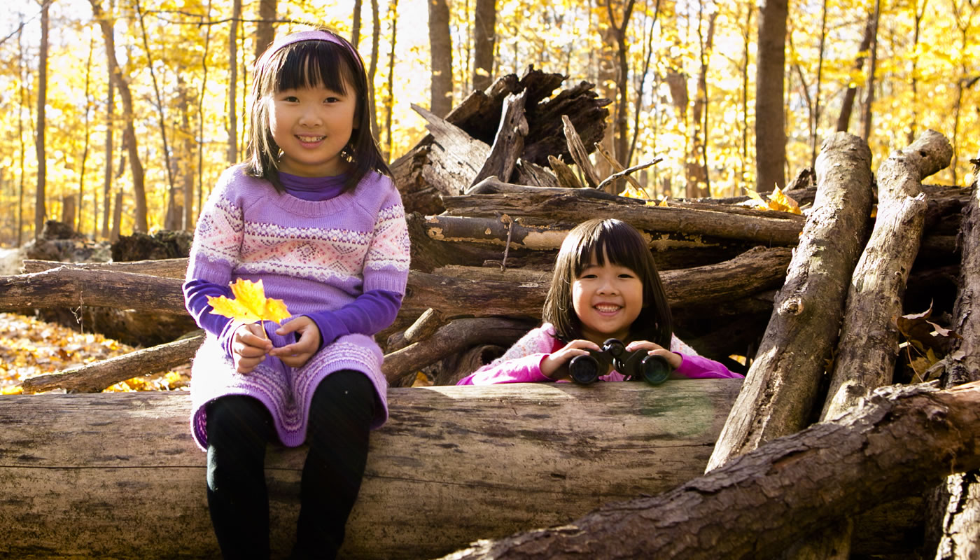 two children playing on a log at River Trail Nature Center