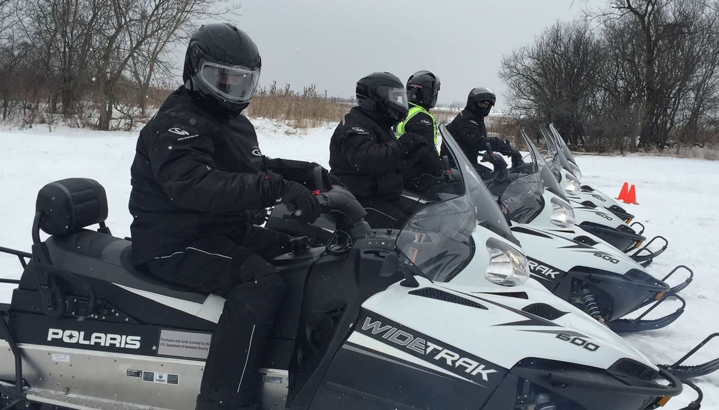 four people on snowmobiles