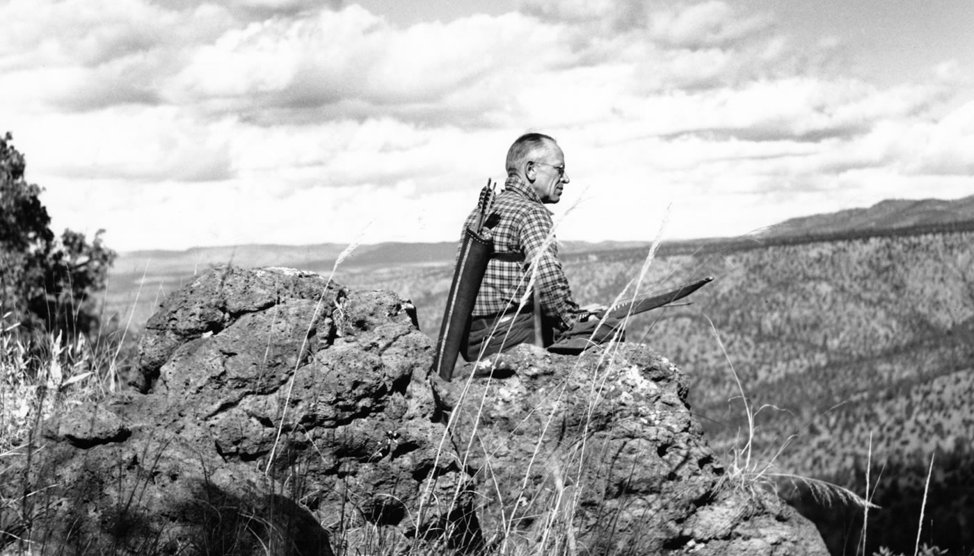 Aldo Leopold sitting on a rock and looking into a valley at Rio Gavilan