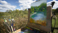paint brushes and a canvas outside at Crabtree Nature Center