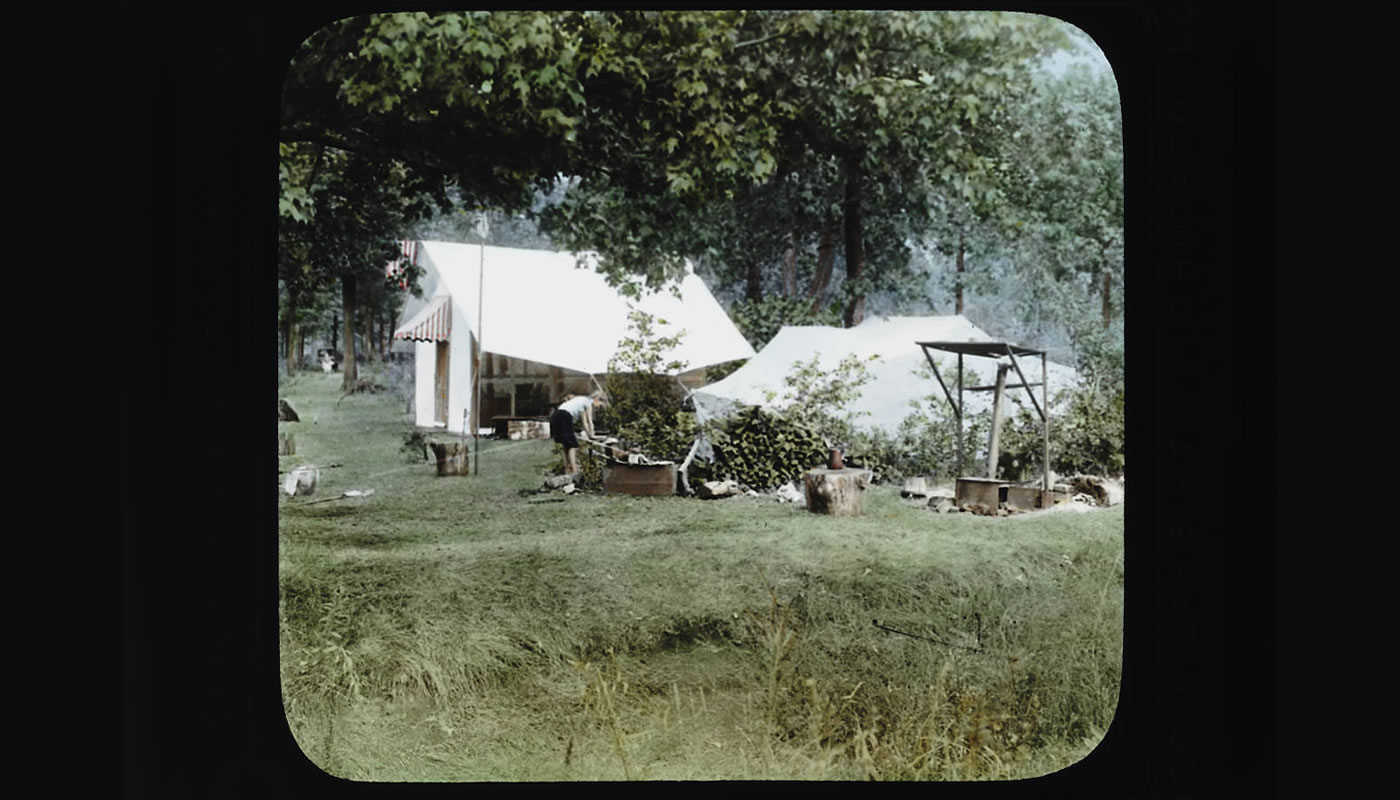 a group of tents set up in the woods in the 1920s