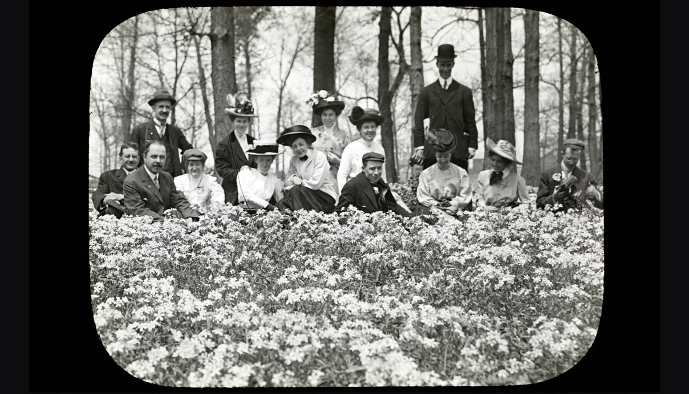 men and women sitting in a field of flowers around 1900