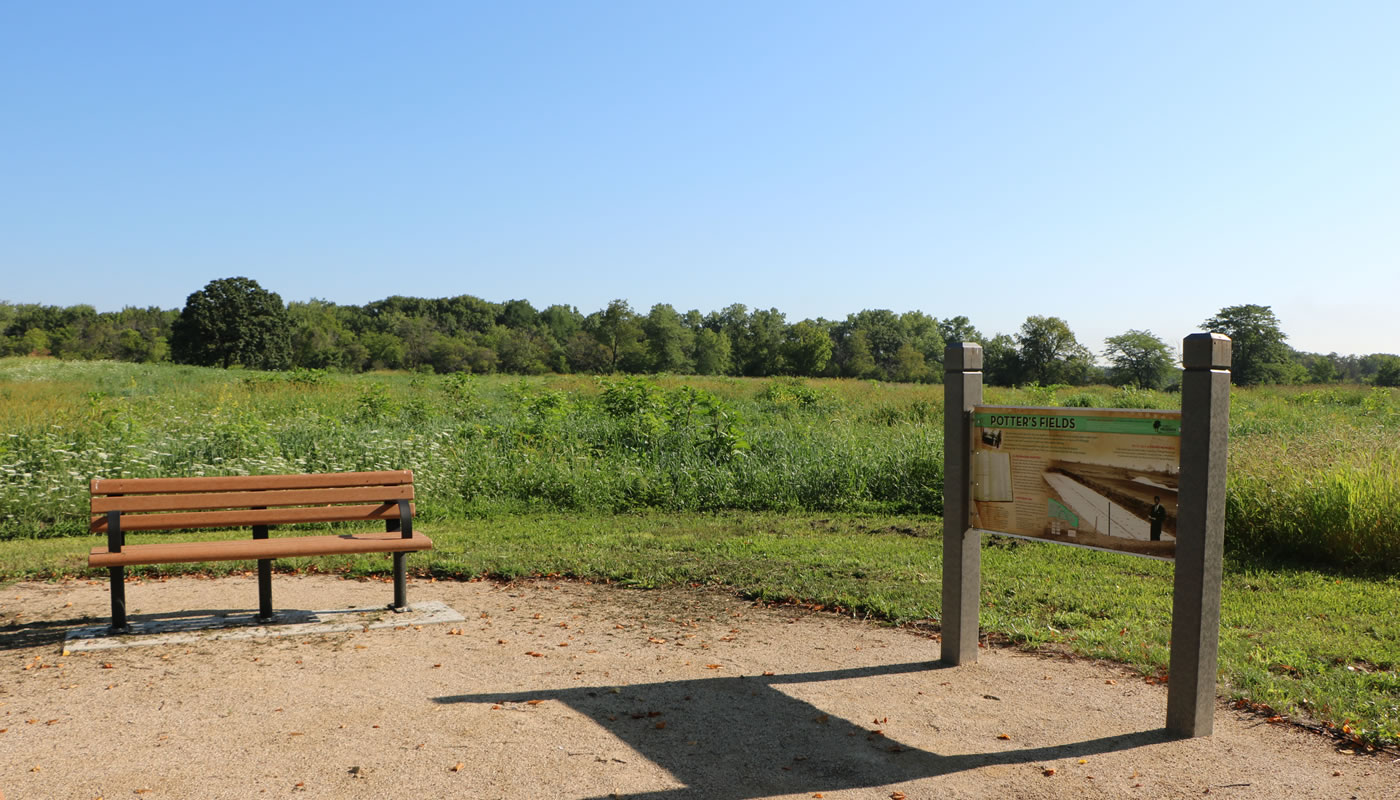 a bench and interpretive sign in front of a prairie at Oak Forest Heritage Preserve.