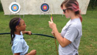a Forest Preserves staff member teaching a girl the parts of an arrow