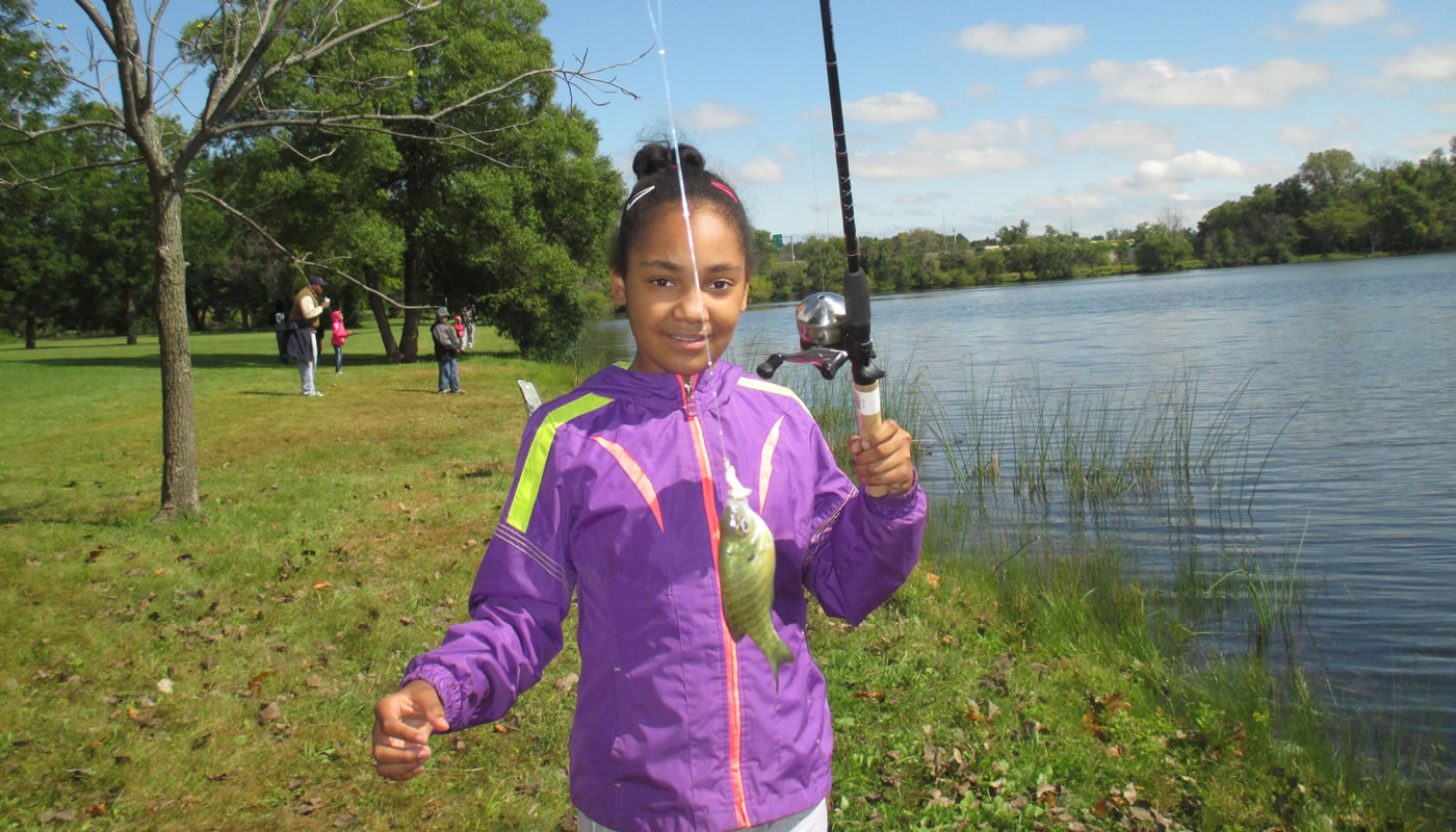 a girl holding up a fishing pole and fish in front of a lake
