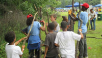 children building a shelter out of tree branches