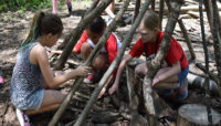 three children building a fort out of logs