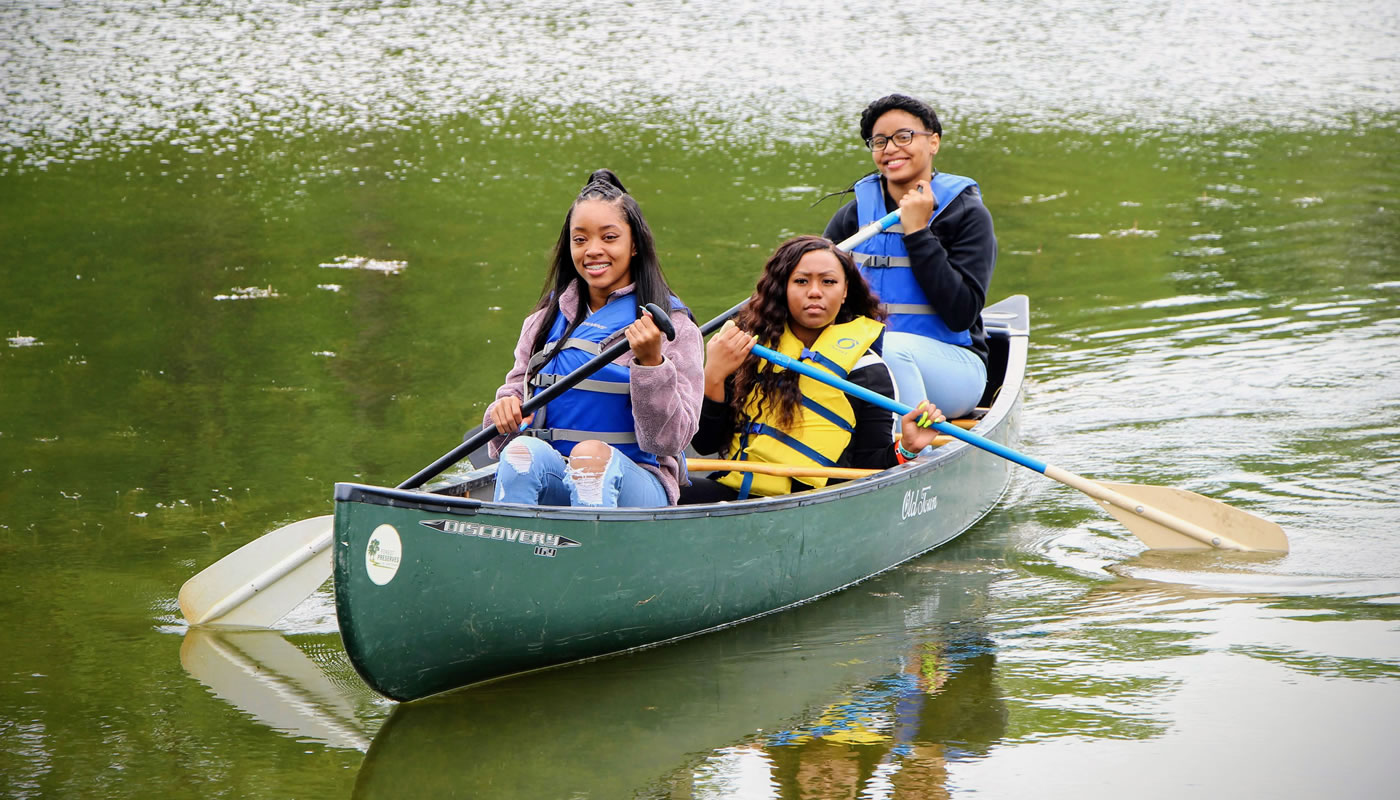 three people in a canoe at Beaubien Woods