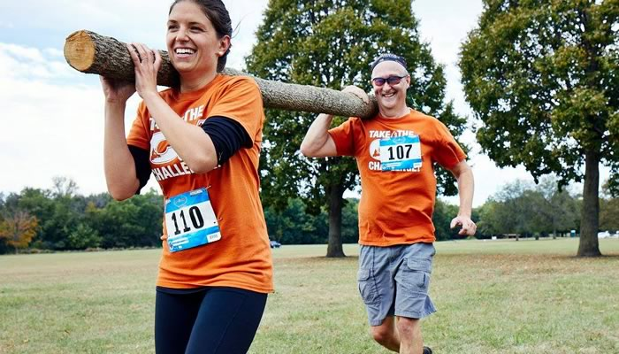 two people running while holding a log on their shoulders