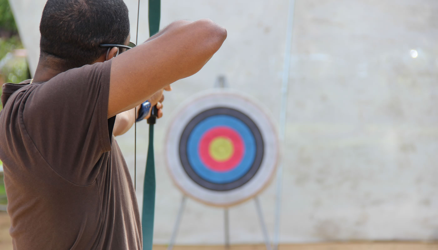 a person taking aim with a bow and arrow