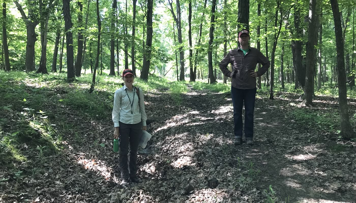 two Forest Preserves staff members, one standing on a trail, one standing below in an area with erosion issues