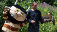 a character from Where the Wild Things are and a staff member with a red tailed hawk
