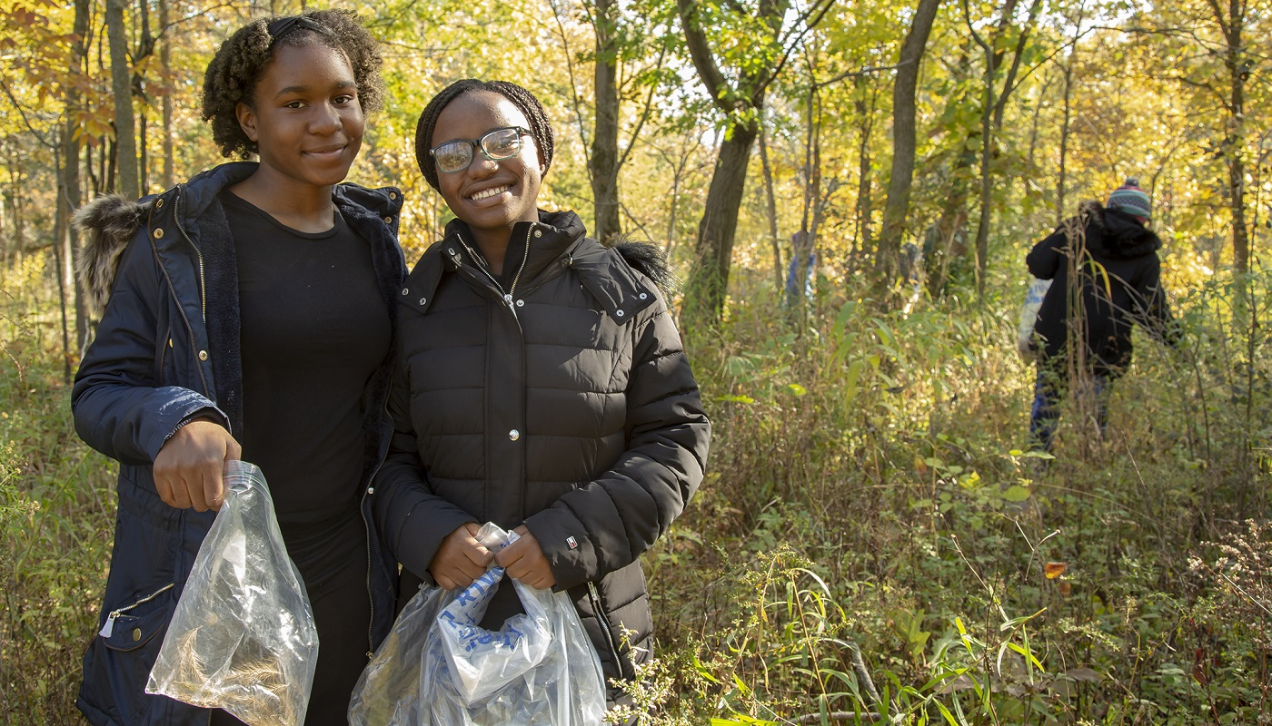 Two youth volunteers collect seed.
