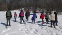 a group of people walking on snowshoes at Caldwell Woods