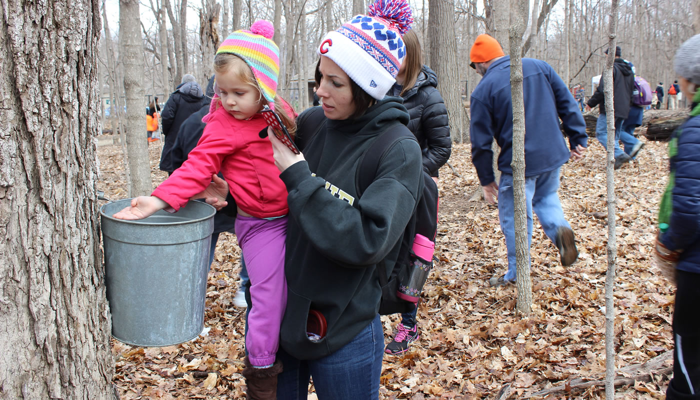 a mother and child exploring a sap bucket at River Trail Nature Center