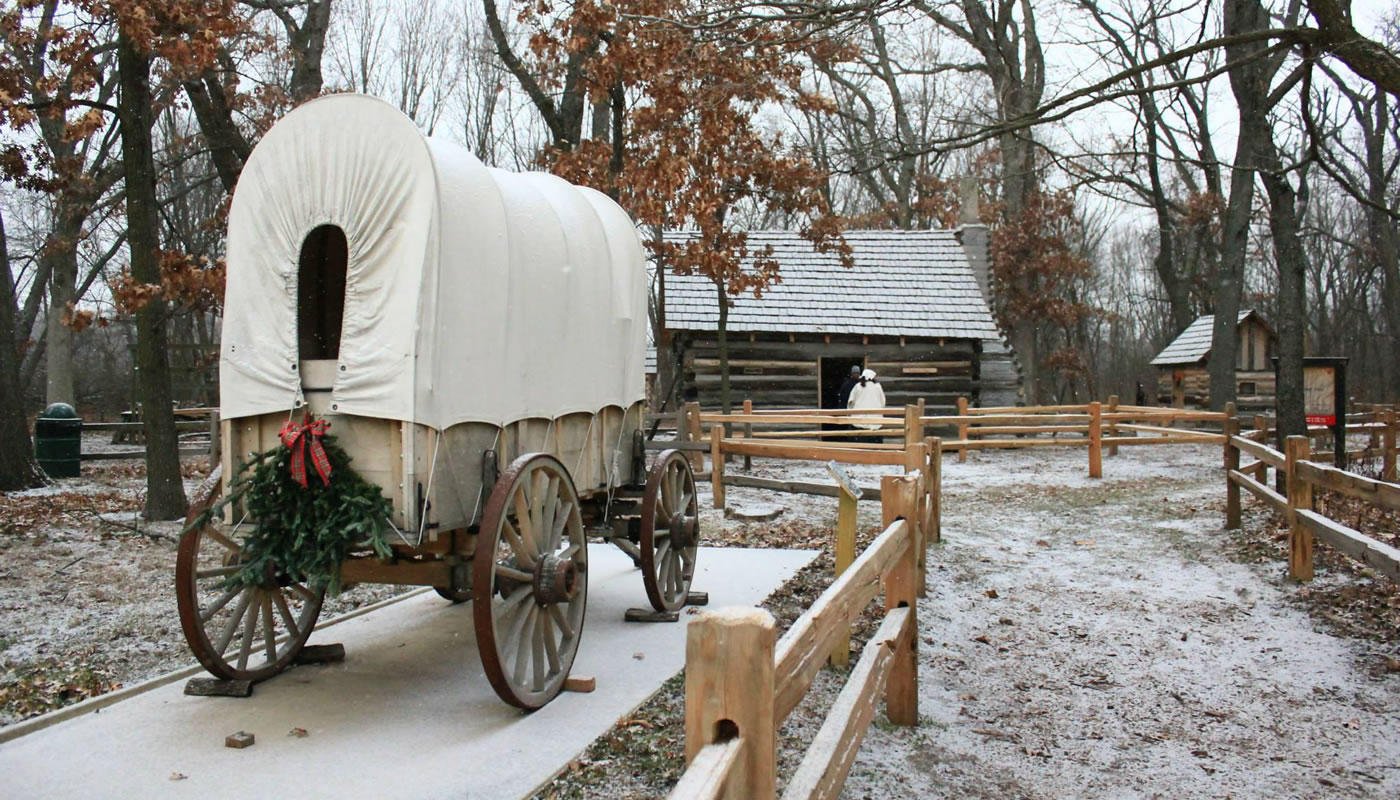 a replica pioneer wagon decorated for Christmas at Sand Ridge Nature Center