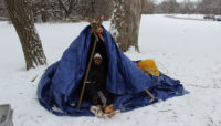 a person in a survival shelter in the snow at Whistler Woods