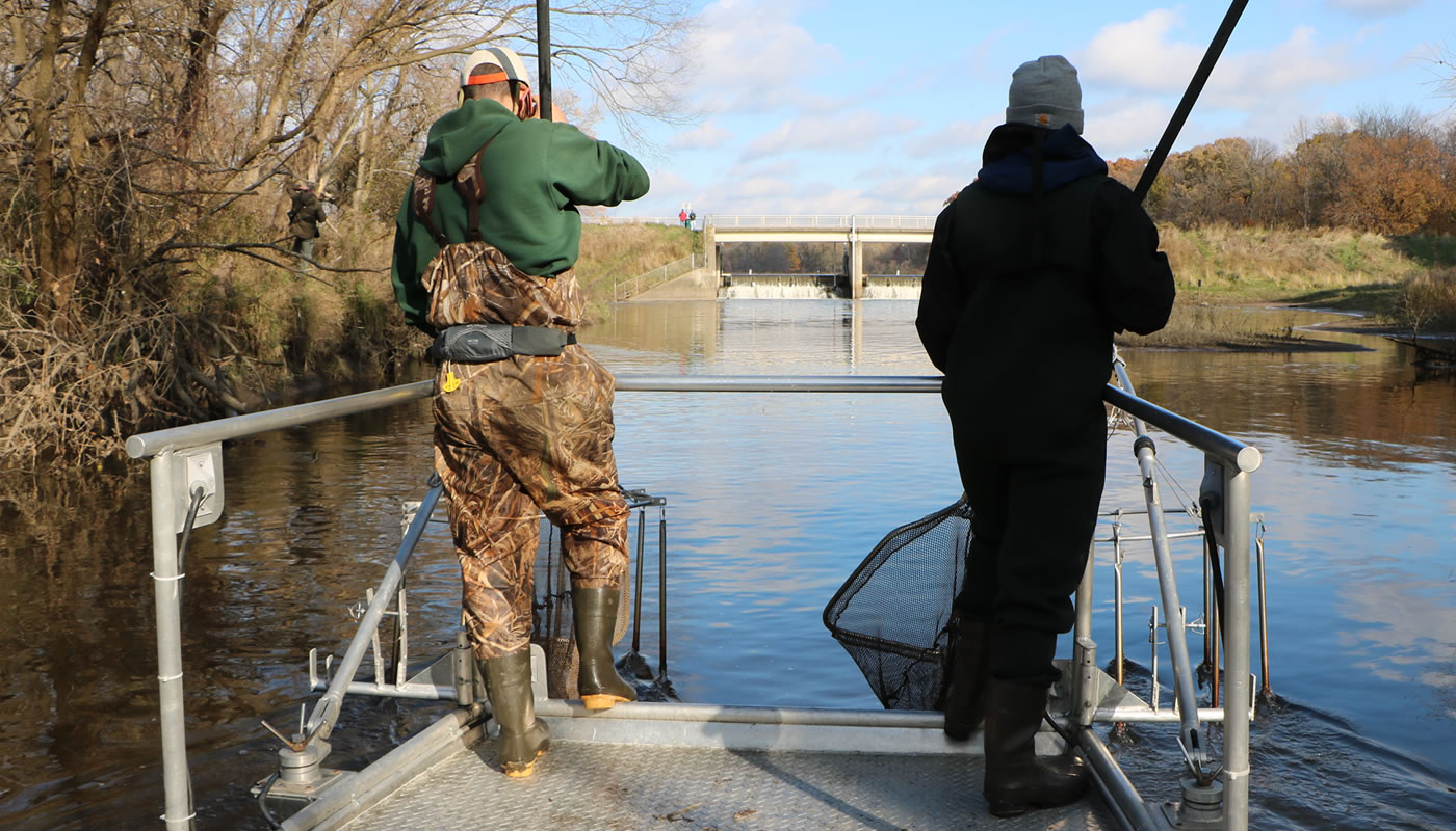 two staff members with nets on the front of a boat near the Busse Reservoir main dam