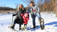 a family snowshoeing at trees and ground covered with snow at River Trail Nature Center
